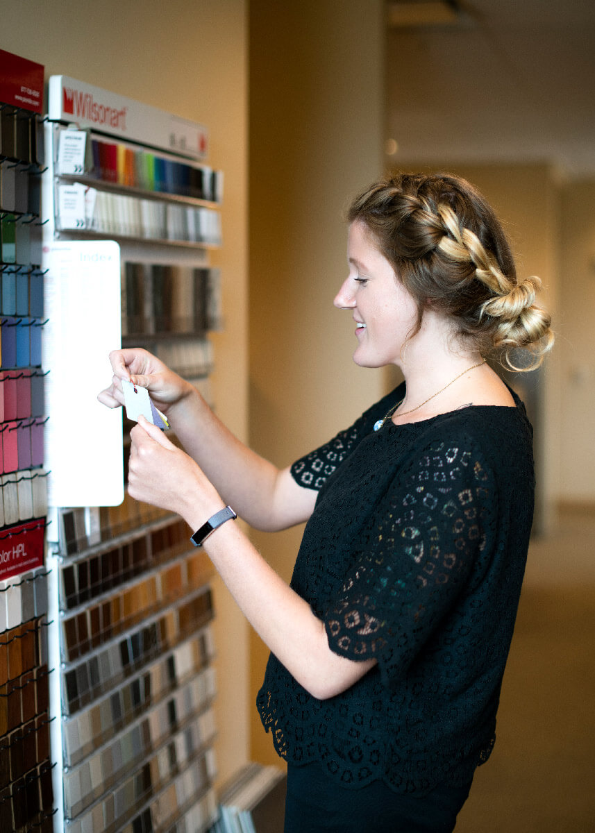 interior designer selecting colors from a multi-color wall of finish samples