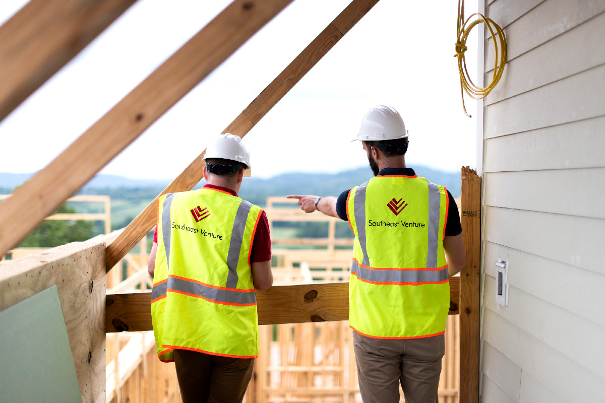 two architects at multi-family project construction site pointing out details