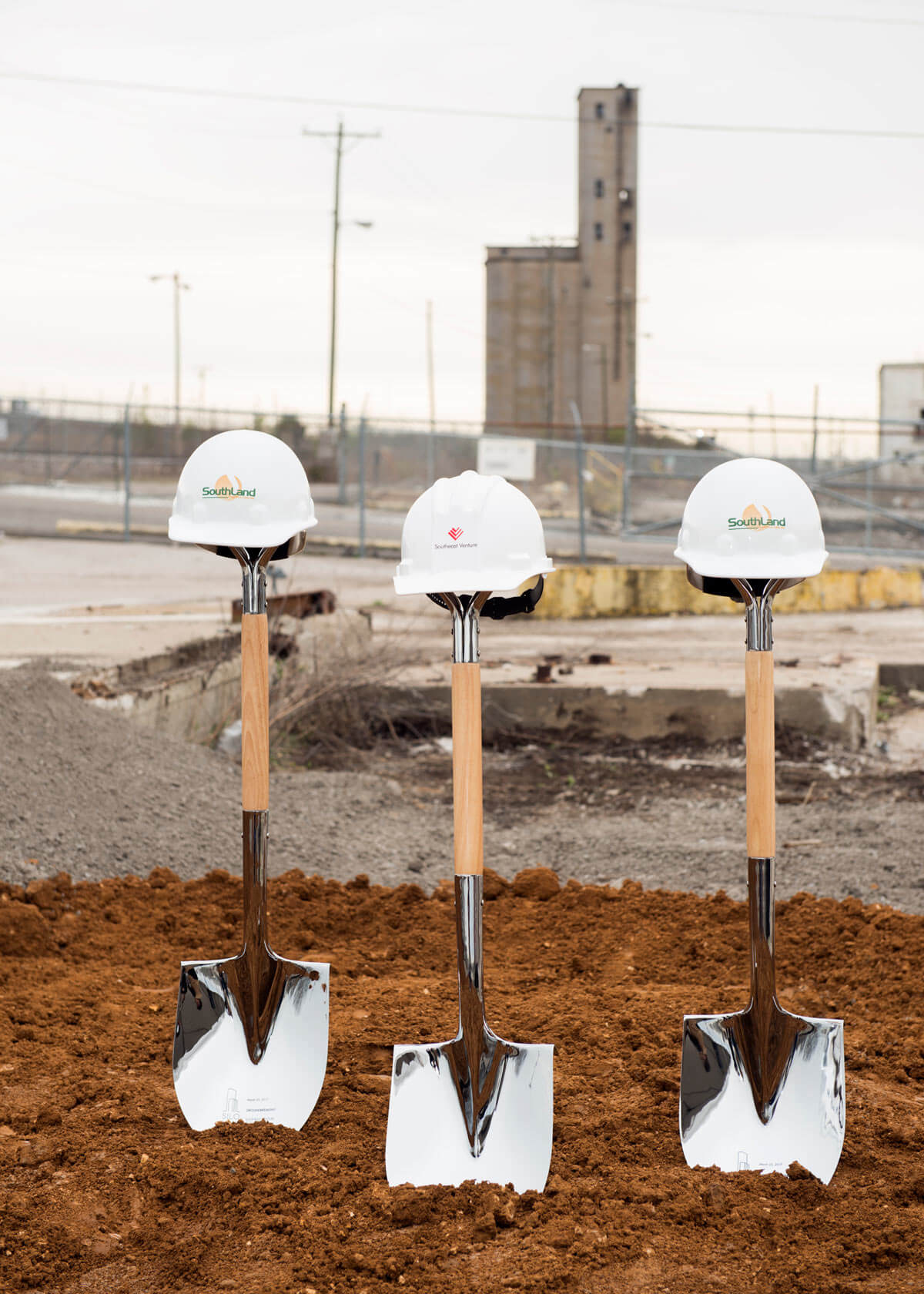 Silo Bend groundbreaking shovels and hardhats in dirt with the Silo in the background